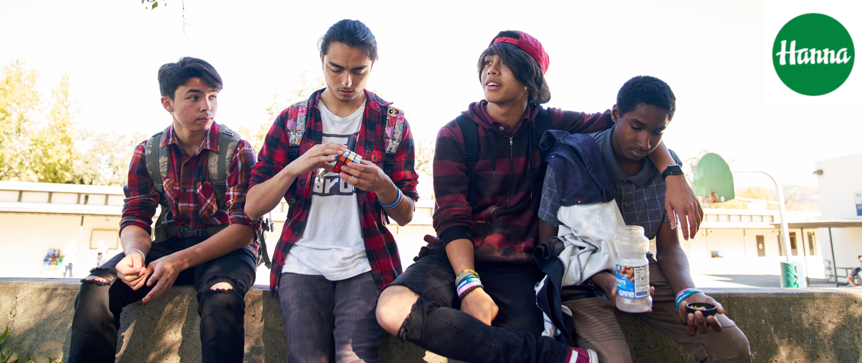 Four young men sitting together in front of campus